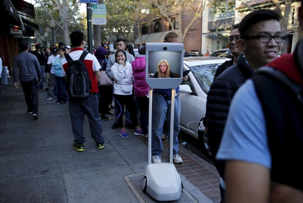 "Brianna Lempesis, from San Diego, appears on a video screen on her ""Beam"" robot, while waiting in line to purchase an iPhone6S at the Apple Retail in Palo Alto,"
