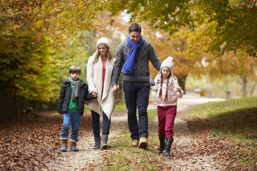 Family Walking Along Autumn Path