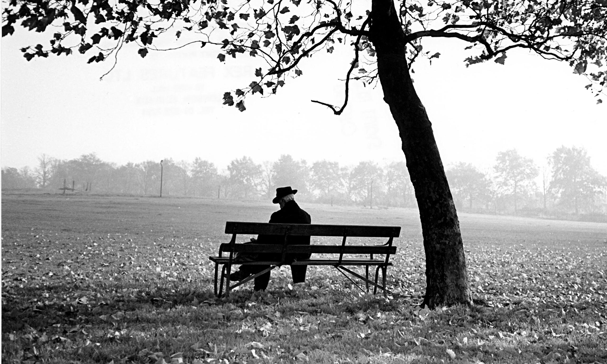грустный человек, сидящий под осенним деревом.