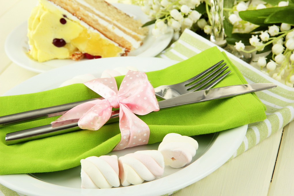 Table setting in white and green tones on color wooden backgrou