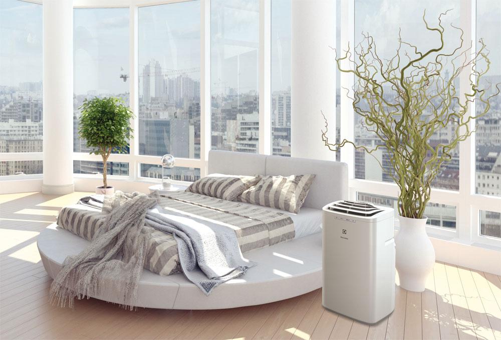 В чём отличие сплит-систем от других типов кондиционеров - мобильный кондиционер около кровати
