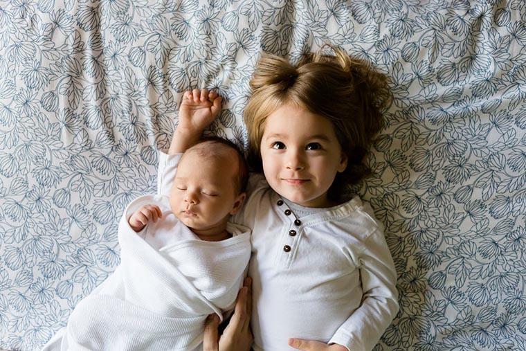 Двое детей на сером покрывале