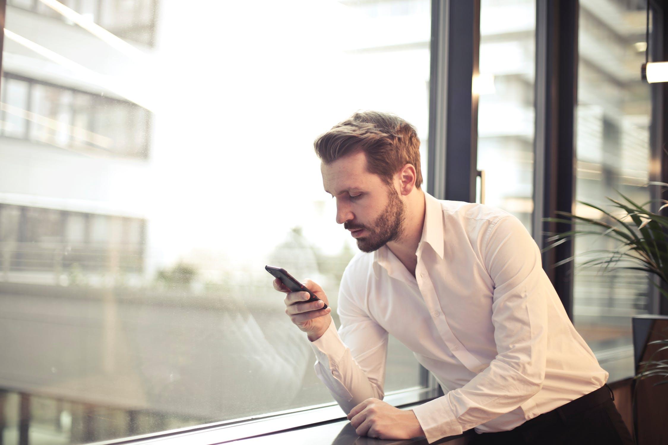 Топ недорогих смартфонов, которые неожиданно хороши - мужчина со смартфоном