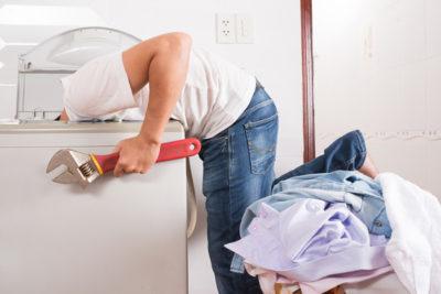 «Чоловік з інструментом заглядає в пральну машину»