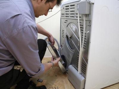 Чоловік щось робить на задній стінці пральної машини