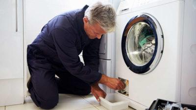 Мастер чистит фильтр стиралки
