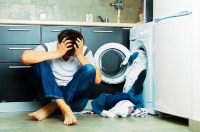 «Молодой мужчииа держится за голову, из стиральной машины выпадает белье»