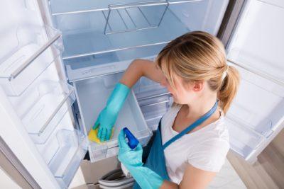Дівчина миє холодильник
