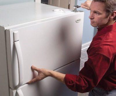 Мужчина снимает дверь холодильника