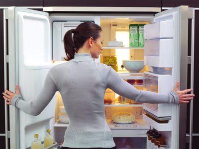 Девушка смотрит внутрь холодильника