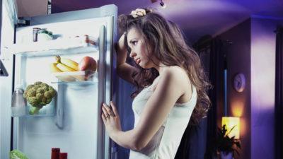Девушка расстроенно смотрит на холодильник