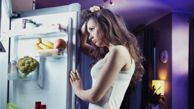 Дівчина засмучено дивиться на холодильник