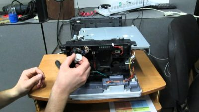 Рука держит белую шестеренку возле разобранного принтера
