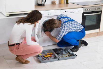 «Девушка и мастер по ремонту стиральной машины смотрят в барабан»