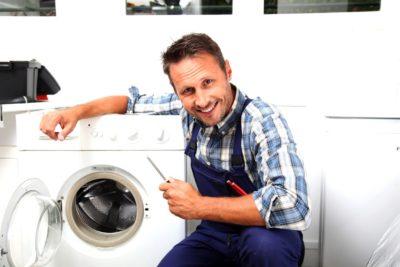 Чоловік посміхається коло пральної машини