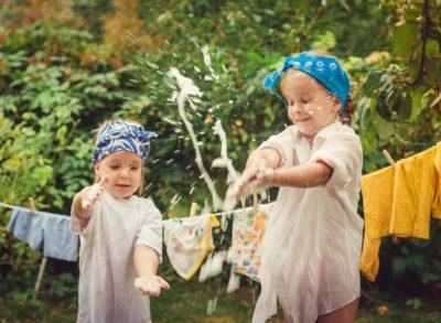 Дві дівчинки грають з водою та перуть речі вручну