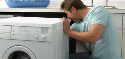 Чоловік біля пральної машини