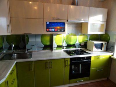 Телевизор встроен в шкаф на зеленой кухне