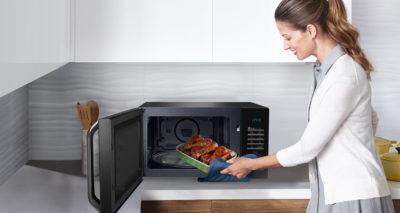 Женщина ставит еду в печь