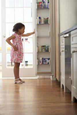 Дівчинка біля холодильника