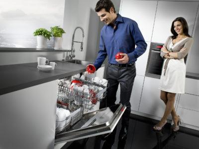 Мужчина загружает посудомоечную машину