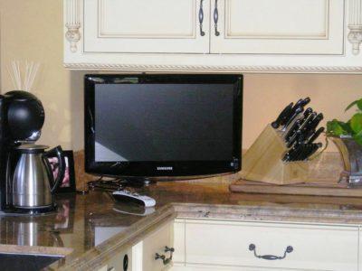 Телевизор на стене коричневой кухни