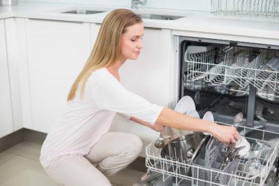 Жінка складає посуд в нижній кошик