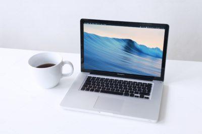 Открытый ноутбук и чашка кофе на столе