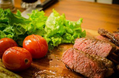 Говяжий стейк, помидорчики и салат на доске