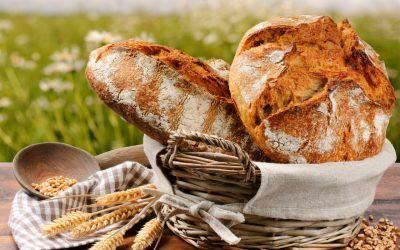 Хлеб в корзине на столе с пшеницей
