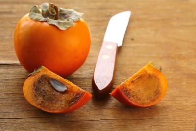 Цілий плід, розрізаний на частини та ніж