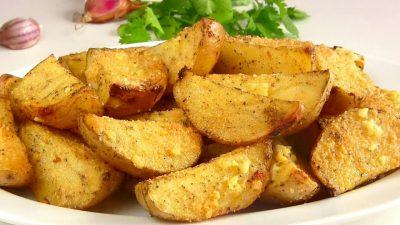 Запеченный картофель дольками на тарелке