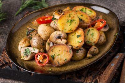 Тарілка з картоплею, грибами й шматочками чилі