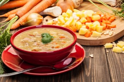 Приготовленный суп из гороха в тарелке красного оттенка