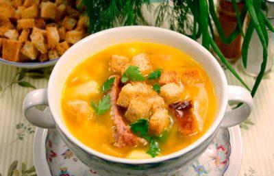 Суп в супнице с копченым мясом и сухариками