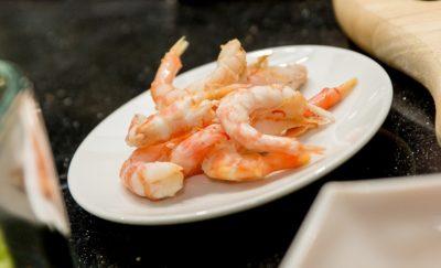 Креветочные хвостики на белой тарелке