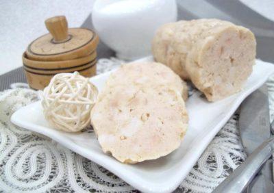 На кружевной салфетке белая тарелка с разрезанной варенкой и декоративном шаром