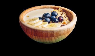 Манная каша в деревянной миске с черникой, бананами, сухофруктами и мюсли