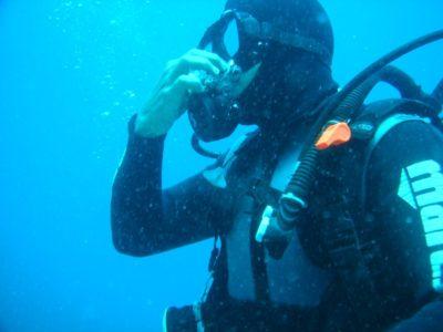 Ныряльщик продувает нос под водой