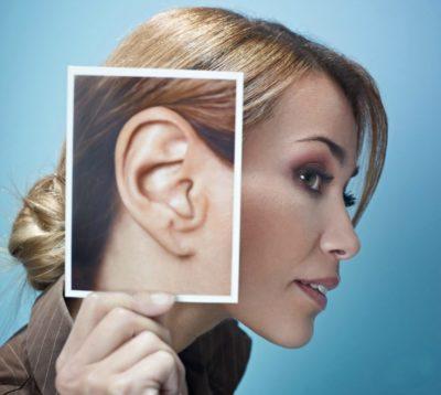 Женщина в профиль держит фотографию уха
