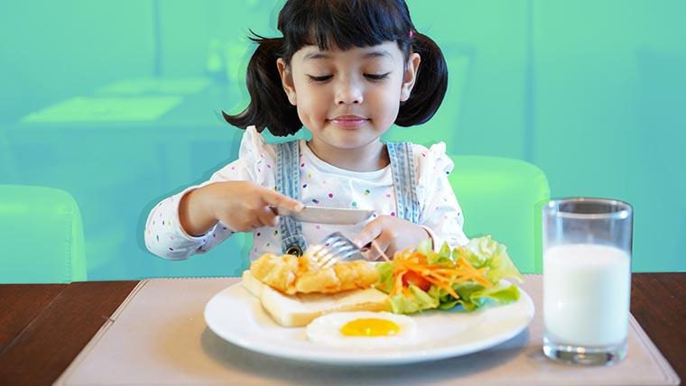 Ребенок ест ножом и вилкой