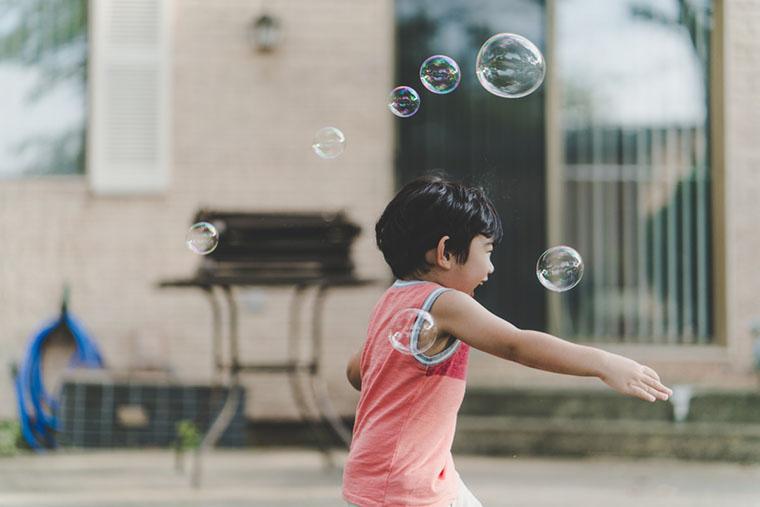 Дитина грає з мильними бульбашками